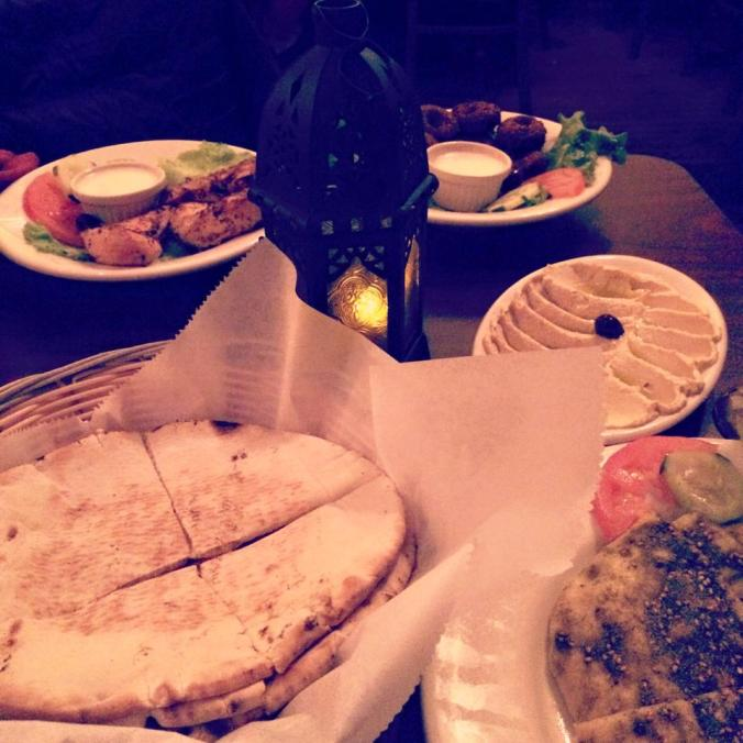 A quick cell phone picture of our Mediterranean feast - hummus and pita bread, Za'atar bread,  falafel and chicken skewers accompanied by a few glasses of a local Riesling.